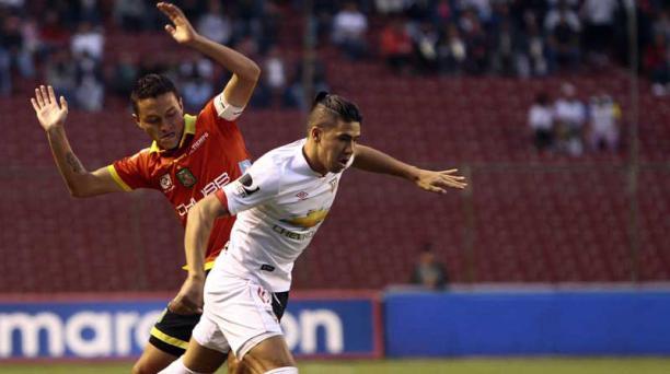 Diego Morales de Liga de Quito pugna por el balón ante la marca de Andrés Oña de Deportivo Cuenca. Foto: API