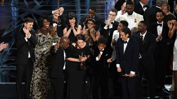 En medio de la confusión por un error en la proclamación de mejor película, el elenco de 'Moonlight' recibe el galardón mayor de la jornada. Foto: Agencia AFP