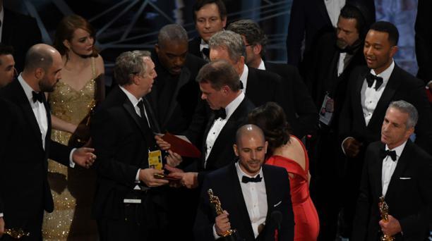 Un productor de espectáculos Oscar (tercero iza.) muestra la tarjeta ganadora al elenco de