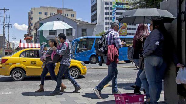 En el sector de la Colón, la gente se protegía ayer del sol. Foto: Armando Prado/EL COMERCIO
