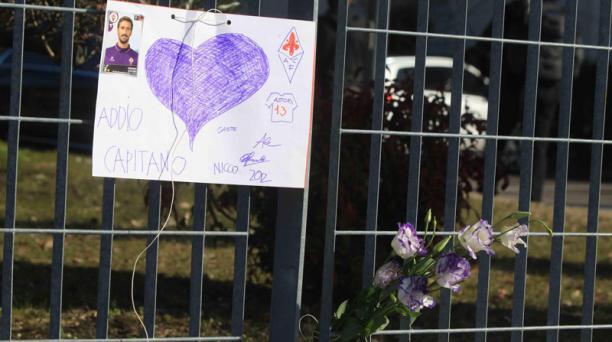 Flores y un cartel en memoria del difunto capitán de Fiorentina, Davide Astori, se observan afuera del hotel donde falleció en Udine, Italia, el 4 de marzo de 2018. EFE