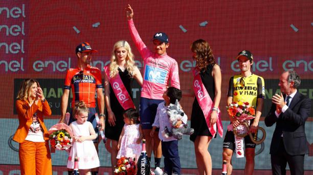 Richard Carapaz en el podio del Giro de Italia, acompañado de sus hijos. También están Vincenzo Nibali (izq.) y Primoz Roglic, el 2 de junio del 2019. Foto: AFP