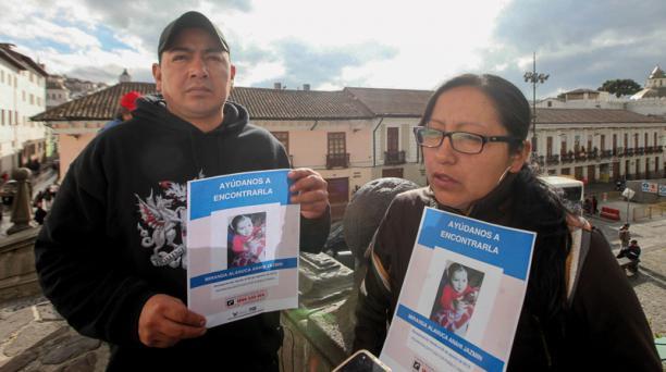 Xavier Miranda y Paola Alanuca, padres de la menor desaparecida en Quito, enseñan los afiches con la foto de su hija y piden que la devuelvan.
