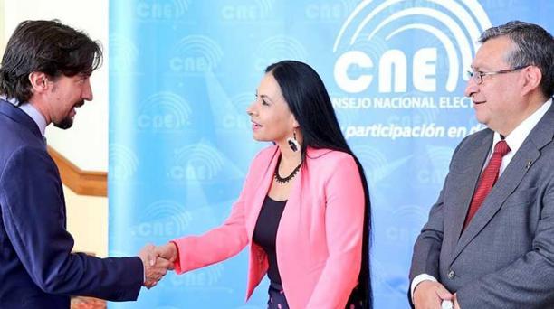 Diana Atamaint y José Cabrera (der.), del CNE, con un miembro del Cuerpo Consular. Foto: cortesía CNE