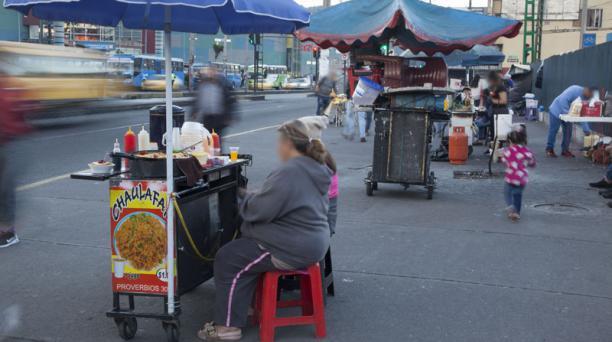 Comerciantes venezolanos venden comida en los exteriores de una parada de bus en Quito. Foto: Armado Prado / EL COMERCIO