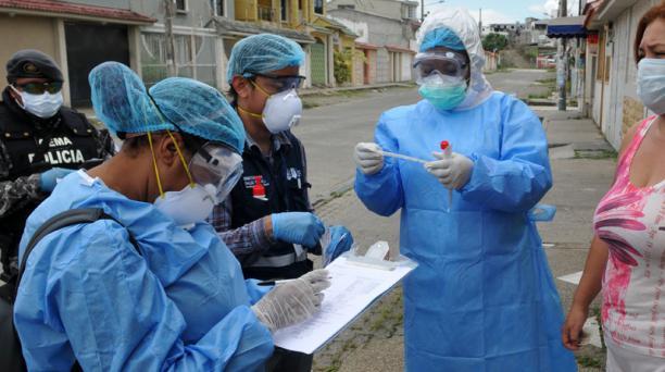 El personal del Ministerio de Salud examina a una mujer en el complejo residencial Samanes 7 en el norte de Guayaquil, Ecuador. Foto: AFP