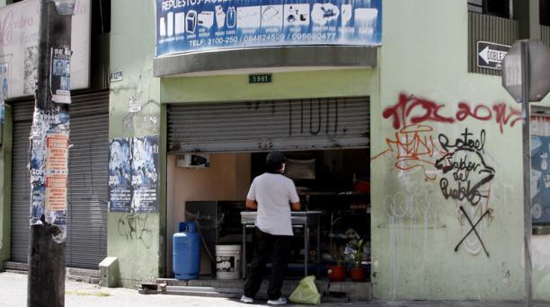 Uno de los locales de Quito que atendieron desde este mes con la puerta semiabierta.