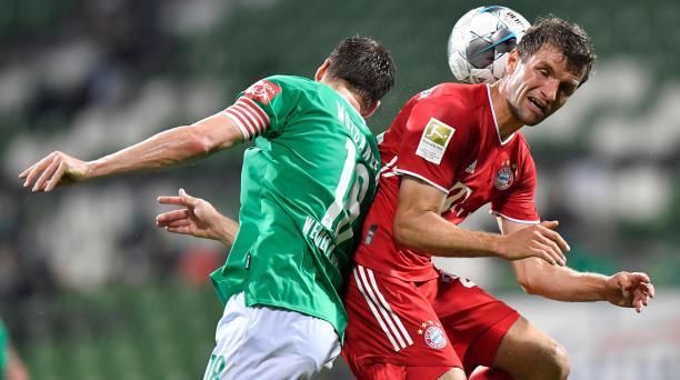 Niklas Moisander (izquierda) trata de cabecear ante la marca de Thomas Müller. Foto: AFP