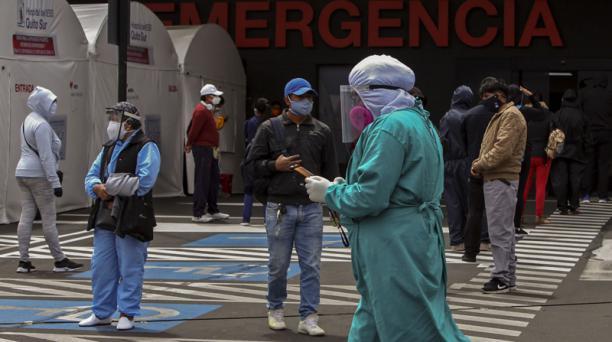Un trabajador de la salud pasa junto a las personas que se encuentran a una distancia de seguridad fuera de una tienda de campaña para el triaje respiratorio y atiende a pacientes con síntomas de covid-19, afuera de la sala de emergencias del Hospital IES