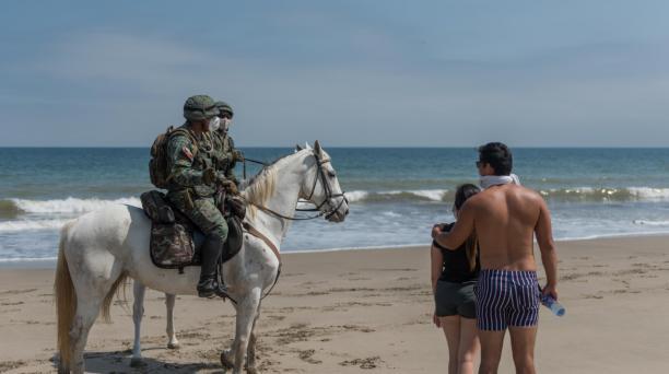 En la playa de Crucita, los policías advertían a los bañistas sobre las restricciones para ingresar al mar, ante la emergencia sanitaria. Foto: Cortesía