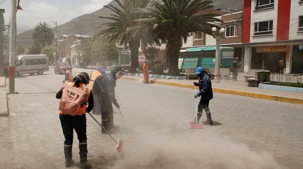 El personal del Municipio de Alausí limpia la ceniza que se acumuló en las calles de la urbe. Foto: Glenda Giacometti / EL COMERCIO