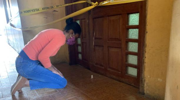 Una mujer deja una vela en la puerta del departamento en donde fueron envenenados dos menores de edad. Foto: Diego Puente / EL COMERCIO
