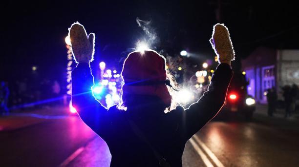 UN manifestante levanta las manos frente a un patrullero en Ferguson. Foto: AFP