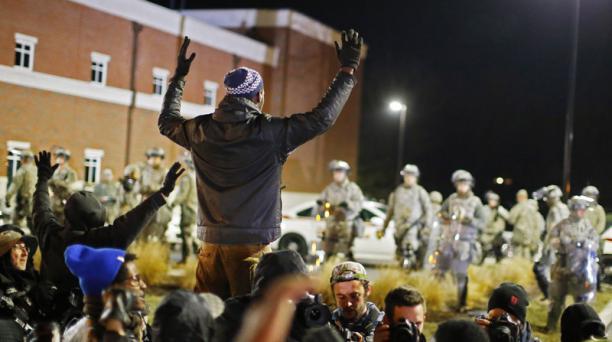 Varios manifestantes permanecen a las afueras del Departamento de Policía de Ferguson
