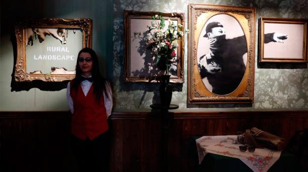 Una recepcionista del hotel muestra dos cuadros apostados en la pared. A la izquierda, se lee la frase
