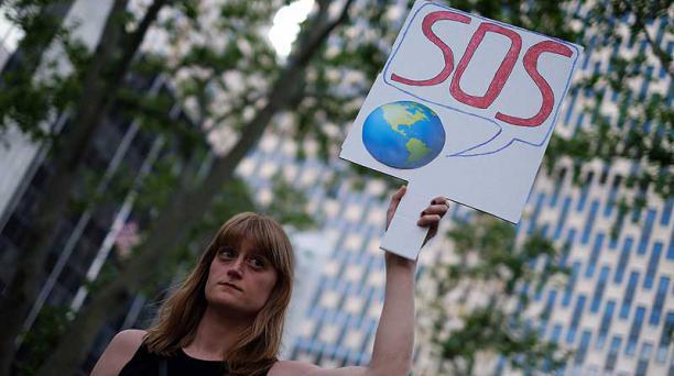 Una mujer exhibe un cartel durante una protesta en Nueva York el 1 de junio de 2017 contra la decisión del presidente de los Estados Unidos de retirarse del Acuerdo de París. Foto: AFP